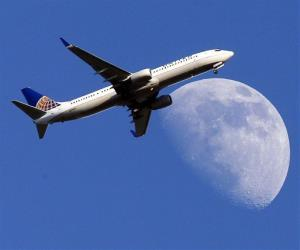 In this July 17, 2013 file photo, a United Airlines jet plane landing at Los Angeles International Airport, in Whittler City  Calif., passes in front of a Waxing Gibbous moon.