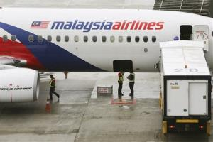 In this May 27, 2014, file photo, ground crew stand near a Malaysia Airlines aircraft on the tarmac at the Kuala Lumpur International Airport (KLIA) in Sepang, Malaysia.