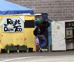 In this Oct. 4, 2013, photo, a person walks by the Right 2 Dream Too homeless camp in Portland, Ore.