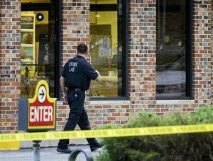 A crime lab technician walks past bullet-riddled windows at a Wendy's in Omaha, Neb., Wednesday.