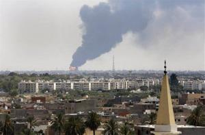 In this July file photo, smoke billows over the Tripoli skyline as a fire at the airport's oil depot rages out of control after being struck in the crossfire of warring militias.