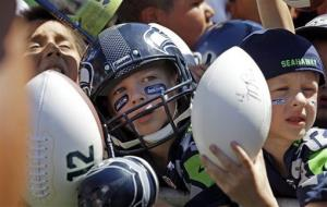 Children wait as Seattle Seahawks quarterback Russell Wilson signs autographs after an NFL football camp practice on July 29, 2014, in Renton, Wash.