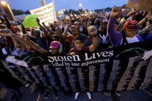 In this Aug. 16 photo, people protest the police shooting death of Michael Brown in Ferguson, Mo.