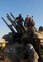 This image posted by the Raqqa Media Center shows ISIS fighters on top of a military vehicle earlier this month.