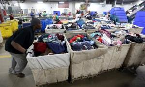 This photo taken April 16, 2014, shows bins of donated clothing being pushed by workers, in the Goodwill plant on Western Avenue in South Bend, Ind.