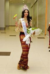 In this June 5, 2014 photo, Myanmar model May Myat Noe waves a miniature flag of Myanmar upon her arrival at Yangon International Airport in Yangon, Myanmar.
