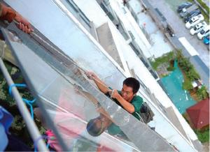 Liu, a worker installing lights, clings to a rope in China's Guizhou province after a boy cut his safety line with a knife.