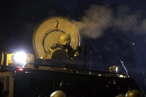 Police fire tear gas from atop an armored personnel carrier in Ferguson, Mo., last month.