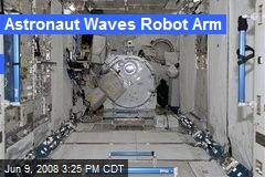 Astronaut Waves Robot Arm